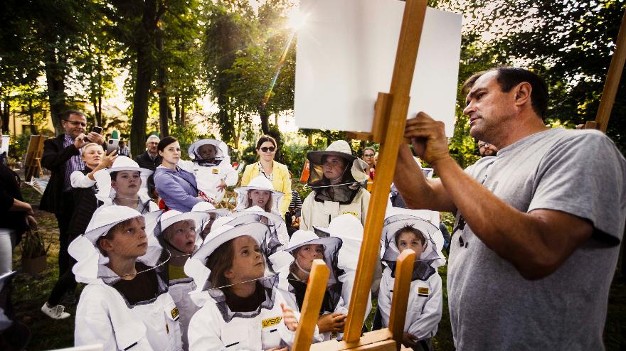 dzieci w pszczelarskich strojach z uwaga wpatrują się w mężczyznę wskazującego na białą kartę na sztaludze