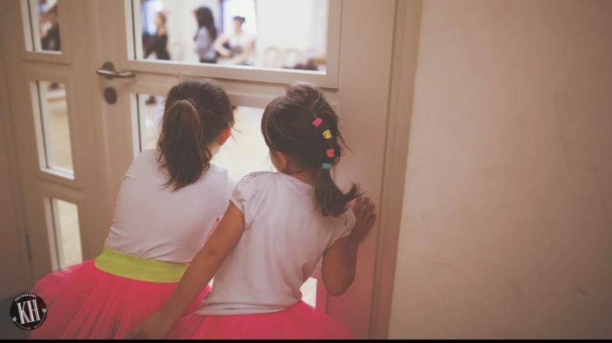 Dwie dziewczynki w różowych baletowych spódniczkach spoglądają przez szybę w drzwiach. foto: Katarzyna Straube