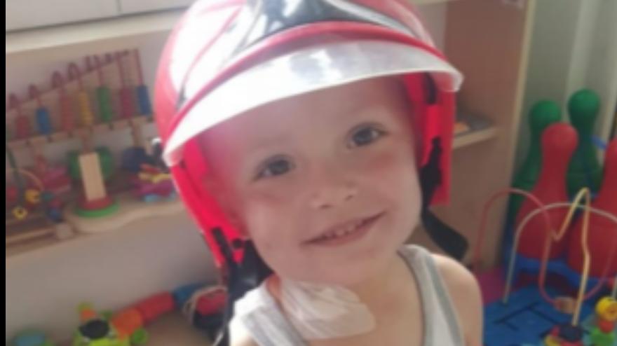 trzyletni uśmiechnięty chłopczyk z czerwonym kaskiem na głowie, na rączce widać założoną kroplówkę